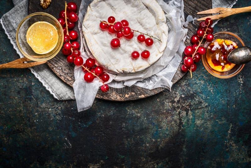 Piatto di formaggio maturo del camembert con le bacche e la salsa del ribes su fondo rustico scuro, vista superiore fotografia stock