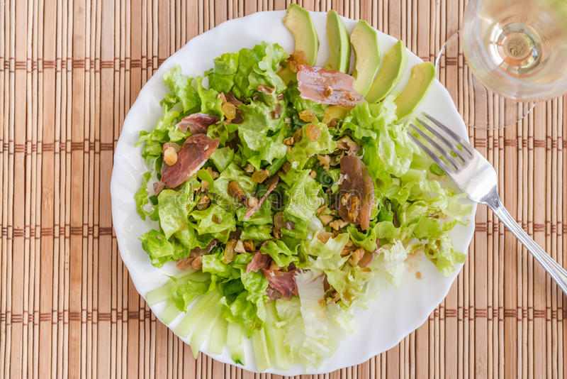 Piatto di insalata verde della miscela con l'avocado, il prosciutto di Parma, l'uva passa ed i pecan sopra la stuoia di bambù immagine stock