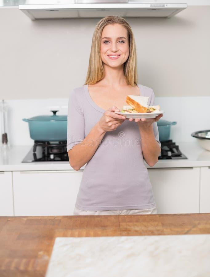 Piatto di modello splendido felice della tenuta con il panino fotografia stock libera da diritti