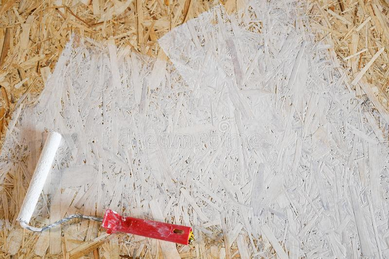 Piatto di Osb dipinto con pittura bianca con un rullo immagine stock