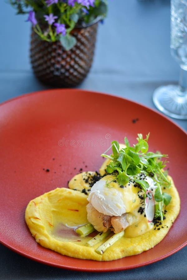 Piatto di pesce con purè sul piatto rosso in ristorante fotografie stock libere da diritti