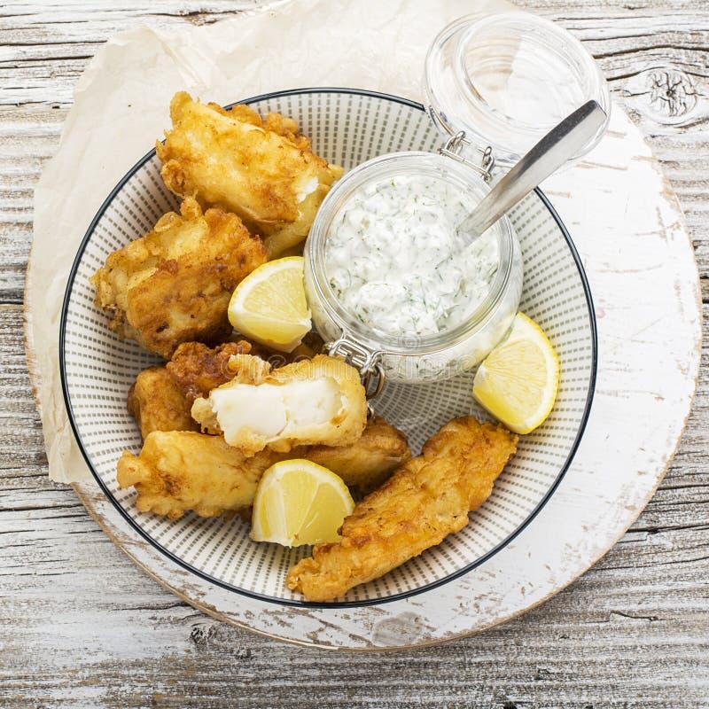 Piatto di pesce - merluzzo nella pastella della birra con la salsa del catrame del catrame per una dieta sana e comoda fotografie stock