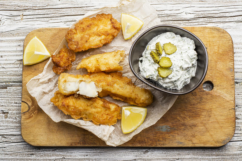 Piatto di pesce - merluzzo nella pastella della birra con la salsa del catrame del catrame per una dieta sana e comoda fotografia stock