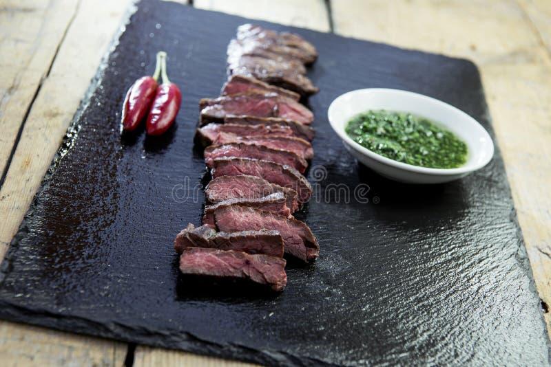 Piatto di pietra nero con il pepe della bistecca di gonna e la salsa di chimichurri immagini stock