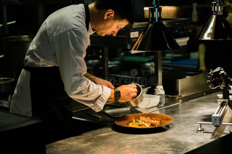 Piatto di placcatura del cuoco unico sul contatore di cucina mentre registrando all'hotel della cucina immagini stock