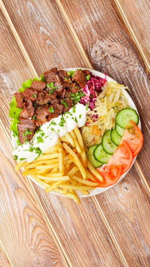 Piatto di Shawarma con manzo, le patate fritte, le verdure e la salsa Disposizione piana fotografia stock