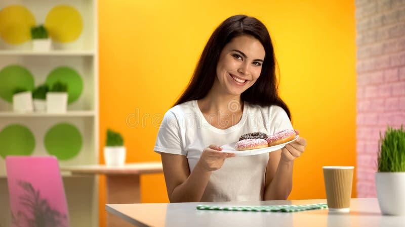 Piatto di tenuta femminile sorridente grazioso con le guarnizioni di gomma piuma a disposizione, dessert saporito, zucchero fotografie stock