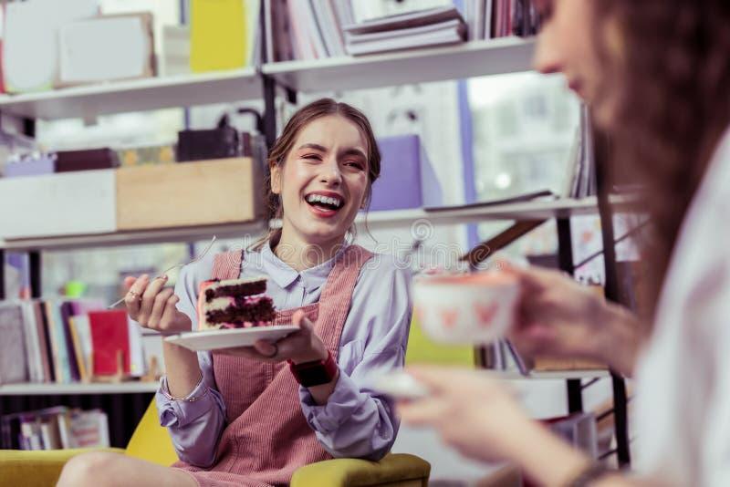 Piatto di trasporto di risata della giovane donna positiva con il pan di Spagna fotografia stock libera da diritti