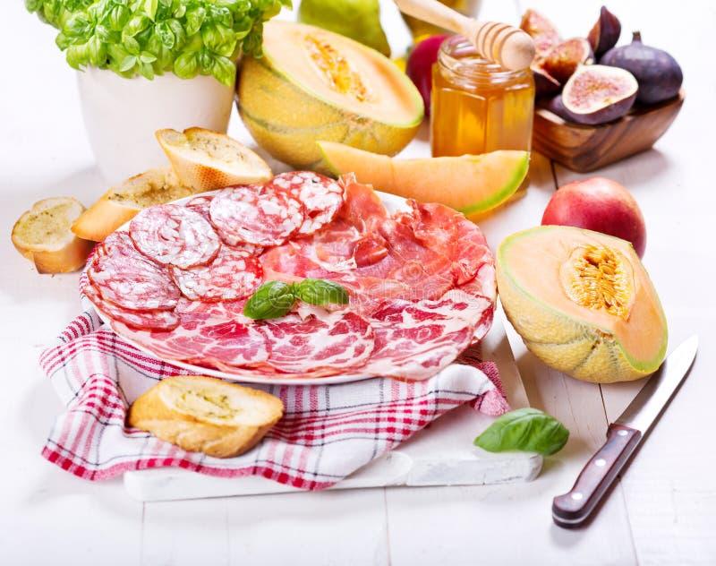 Piatto di vari prosciutto e salame con la frutta fresca immagine stock libera da diritti