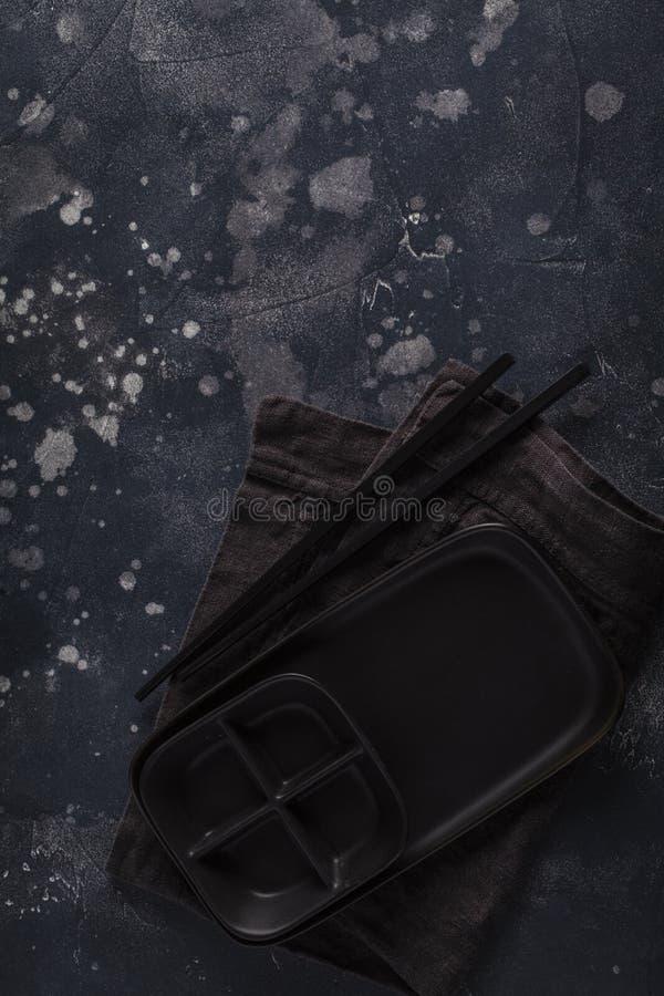 Piatto e bastoncini neri per alimento giapponese su un fondo scuro fotografia stock libera da diritti