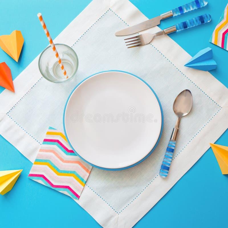 Piatto e coltelleria vuoti su fondo blu bianco concetto del menu dei bambini di un caffè o di un ristorante fotografia stock libera da diritti