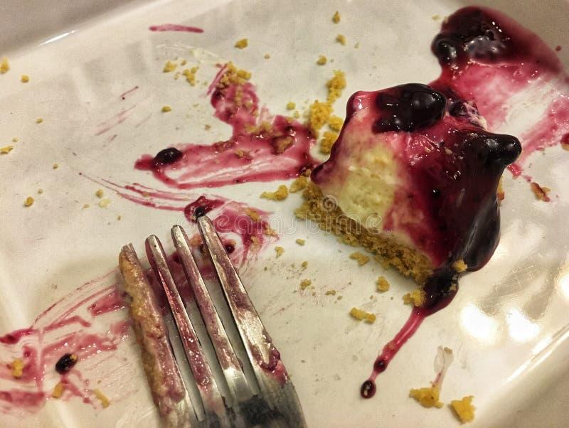 Piatto e forcella della torta di formaggio del mirtillo dopo il cibo di rivestimento fotografie stock