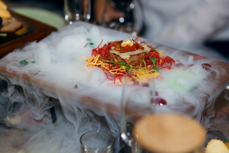 Piatto freddo saporito con le verdure ed il pesce, serviti con azoto liquido fotografia stock libera da diritti