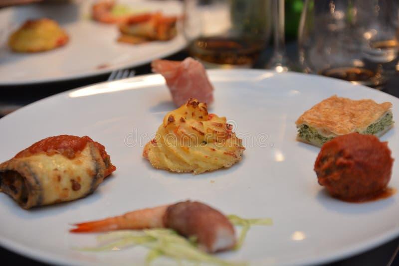 Piatto italiano dell'aperitivo sull'alimento gastronomico di prosciutto di Parma della patata della carne di pesce della melanzan immagini stock libere da diritti
