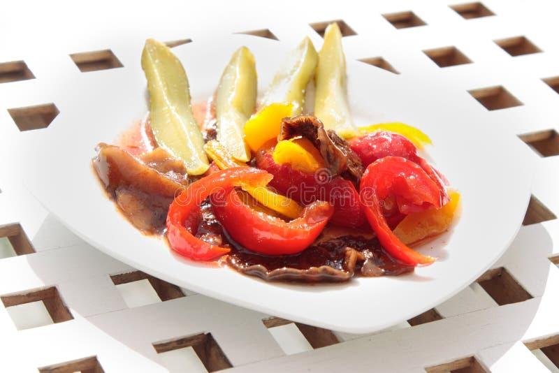 Piatto laterale sul piatto bianco, sull'insalata delle verdure fatta dei pomodori secchi, sui cetrioli marinati e sulla paprica fotografie stock libere da diritti