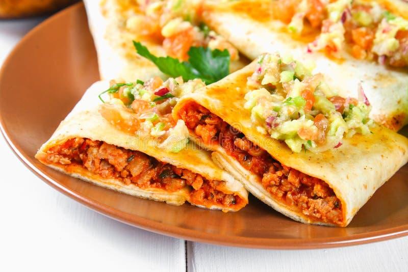 Piatto messicano tradizionale - chimichanga Il dolce di cereale con carne tritata, il pepe, la cipolla, l'aglio, l'origano, lo zi fotografia stock