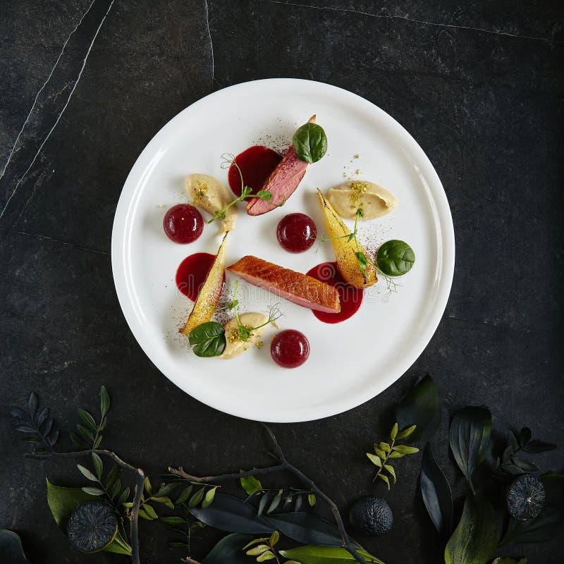 Piatto molecolare creativo servente squisito di Duck Breast, della pera al forno e di Cherry Spheres Top View immagini stock