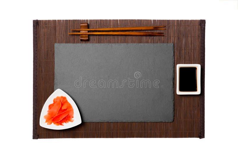 Piatto nero rettangolare vuoto dell'ardesia con i bastoncini per la salsa dei sushi, dello zenzero e di soia sul fondo di bambù s fotografia stock