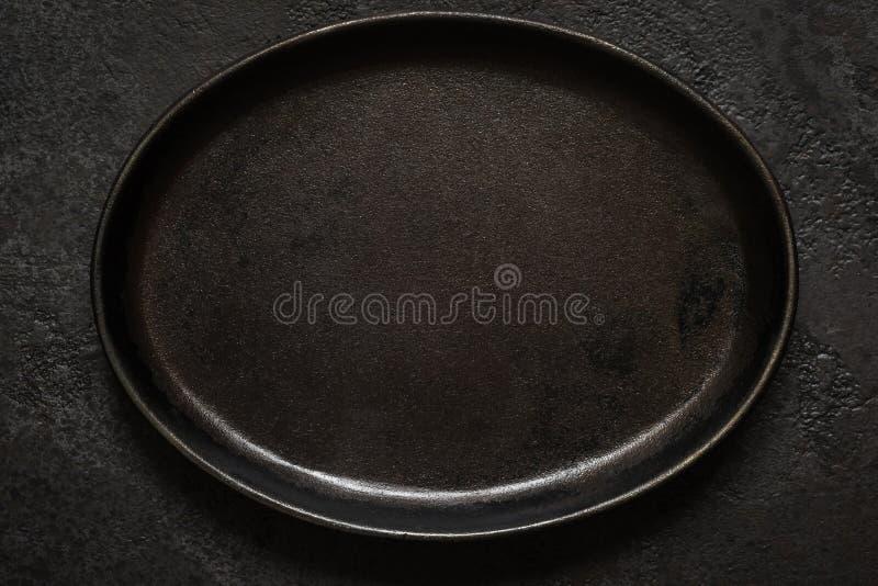 Piatto nero rustico vuoto del ghisa su fondo concreto scuro Vista superiore con lo spazio della copia immagine stock