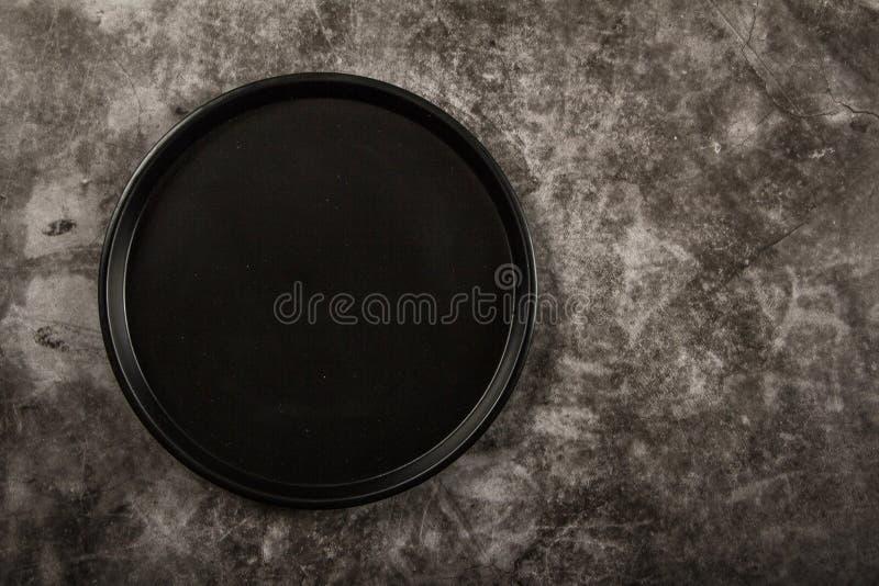 Piatto nero su un fondo grigio Disposizione dei piatti neri su un fondo grigio Vista da sopra fotografia stock