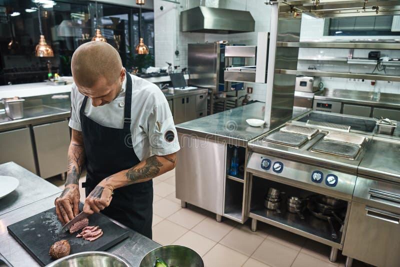 Piatto principale Cuoco unico calvo maschio con i bei tatuaggi sulle sue mani che tagliano una carne mentre stando in una cucina  fotografia stock