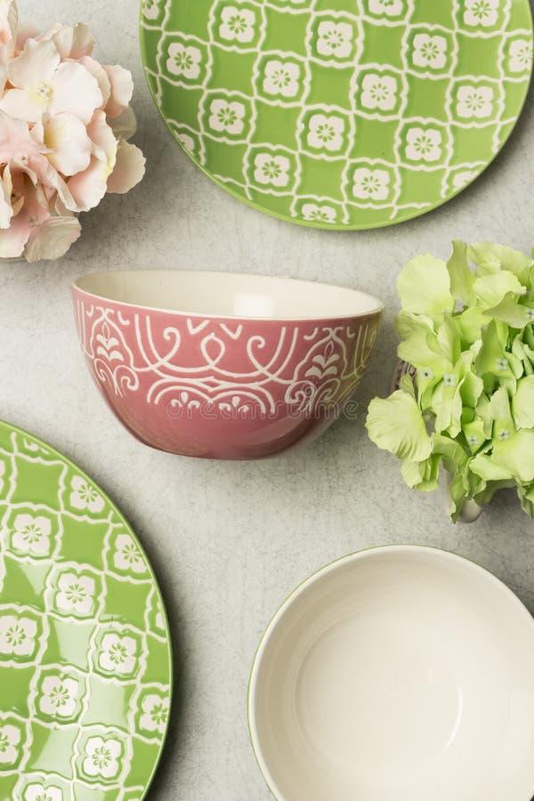 Piatto profondo di ceramica rosa con le incisioni bianche accompagnate dalle placche piane verdi e dai fiori artificiali fotografie stock
