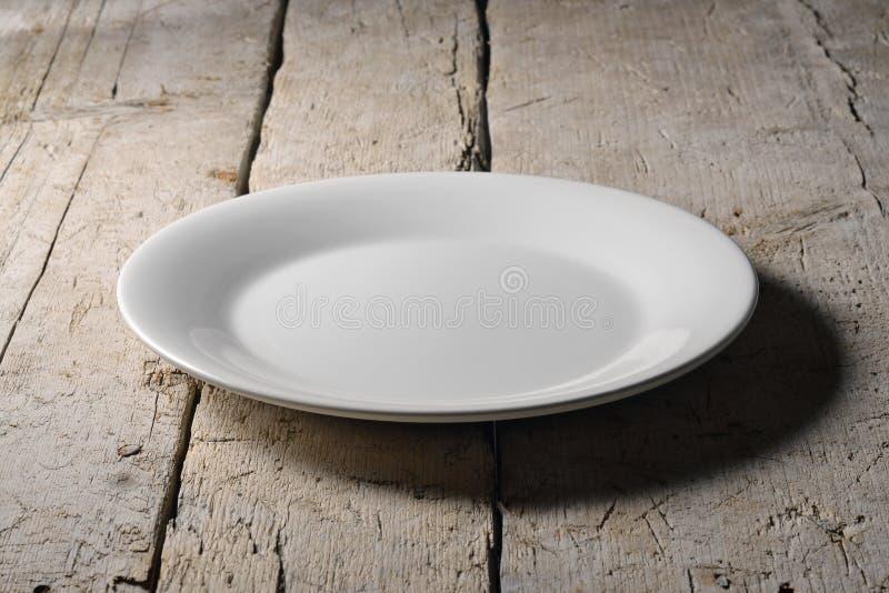 Piatto rotondo bianco vuoto sulla tavola di legno ruvida fotografia stock
