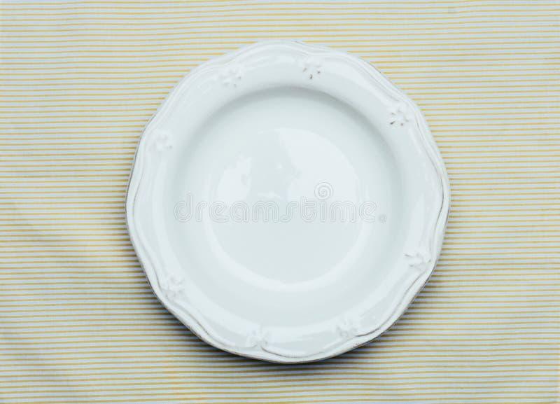 Piatto rustico bianco vuoto sui precedenti di una tovaglia a strisce leggera con un coltello, forcella Concetto rustico dell'alim immagini stock