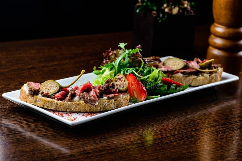 Piatto squisito Il pane fresco con le fette succose della carne è servito con la s immagini stock libere da diritti