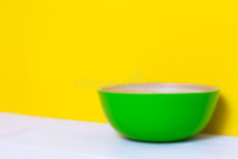 Piatto verde di bambù sulla tavola di legno bianca, fondo giallo della carta di colore, modello di carta, vista laterale, copyspa immagine stock
