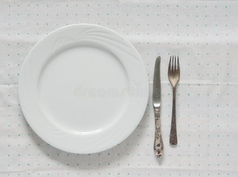 Piatto vuoto bianco con la forcella e coltello su una tovaglia del pois fotografie stock