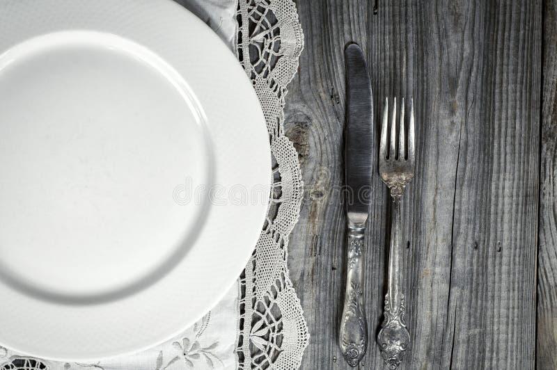 Piatto vuoto bianco sulla tovaglia con pizzo, vicino al coltello ed alle FO immagine stock