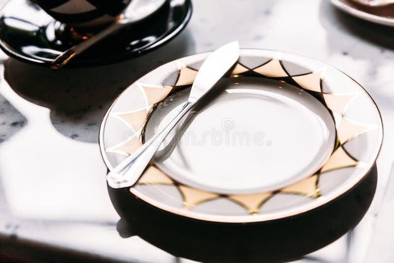 Piatto vuoto brillante del modello dorato e d'argento con il coltello di burro sul tavolo della presidenza di marmo immagine stock