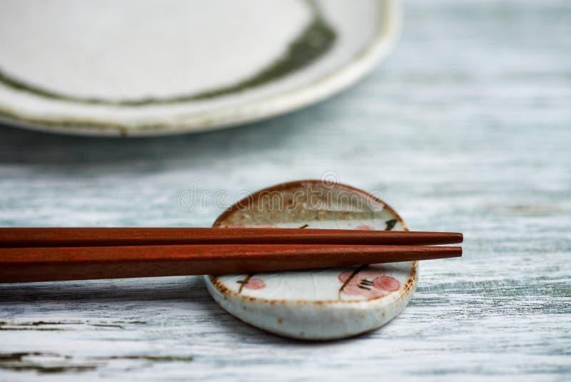 Piatto vuoto della ceramica, bastoncini di legno e resto del bastoncino su fondo di legno rustico immagine stock