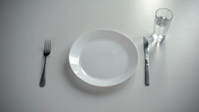 Piatto vuoto servito sulla tavola, vetro con acqua, nessun soldi per alimento, povertà fotografie stock libere da diritti