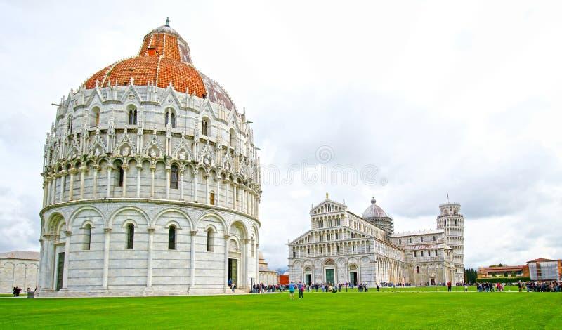 Piazza del Duomo i Pisa, baptisteryen och basilikan, Italien Benägenhettorn i bakgrunden Unidentifiable turister arkivfoto