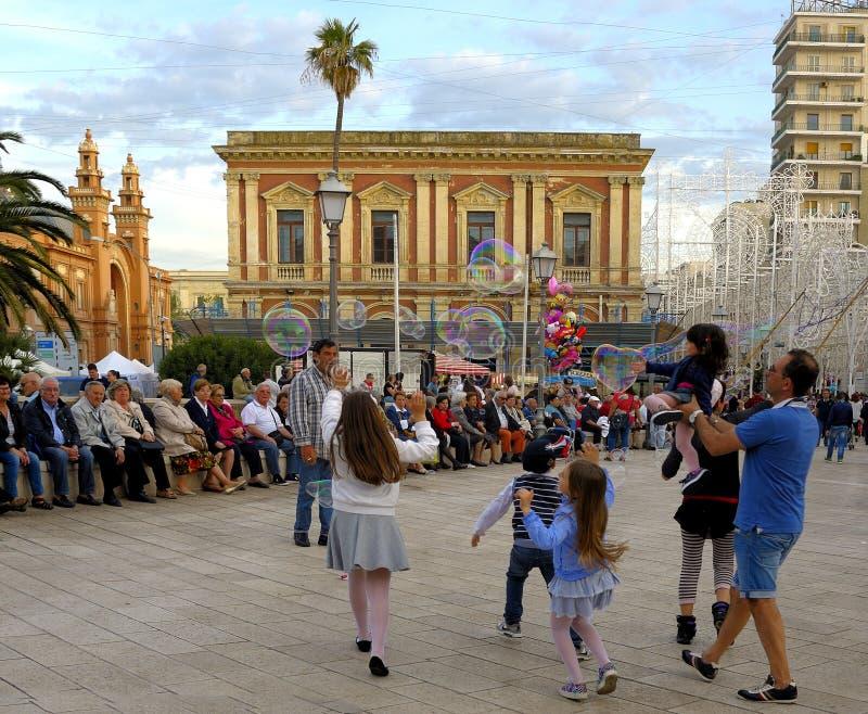 Piazza del Ferrarese与肥皂泡的儿童游戏在圣尼古拉斯期间宴餐  免版税库存图片