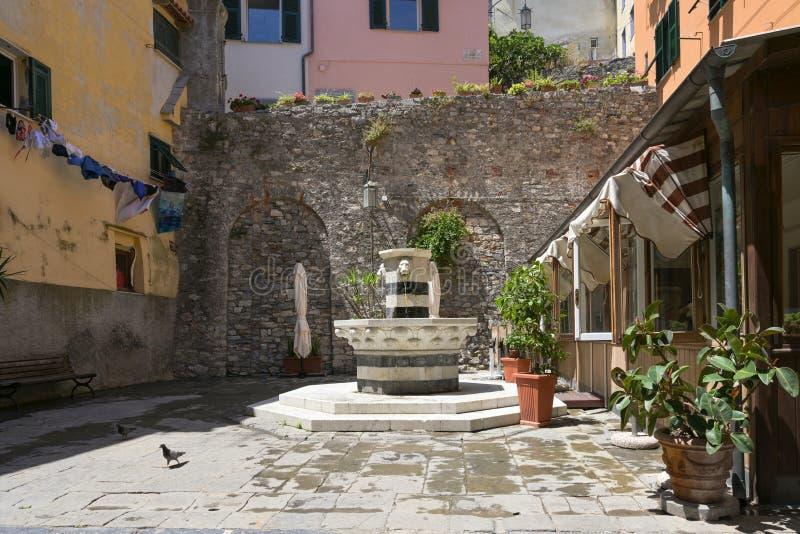 Piazza med en dricksvattenreserv från marmor med lejonhuvuden i den gamla staden Porto venere, Ligurien, Italien royaltyfria foton