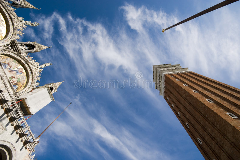 Piazza San Marco. Bottom up view of Piazza San Marco with basilic / basilica, pole and bell tower in a sunny day - shot with an ultra wide angle lens - Venice ( royalty free stock photo