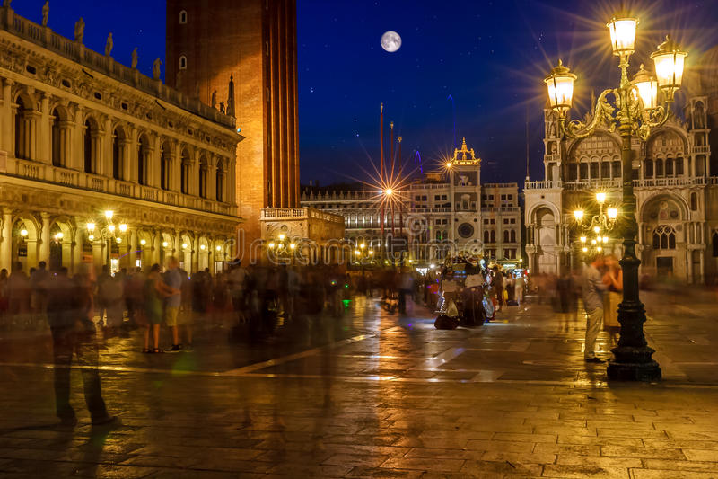 Piazza San Marco, Venedig, Italien som, är upplysta på natten med massor av oigenkännligt folk, färgrik himmel och fullmåne arkivfoto