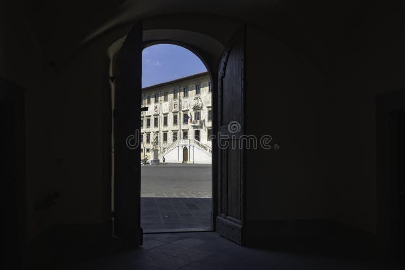 Piazzadeien Cavalieri från halvskuggan av portalen, framme av den Palazzo dellaen Corovana, Pisa, Italien royaltyfri fotografi