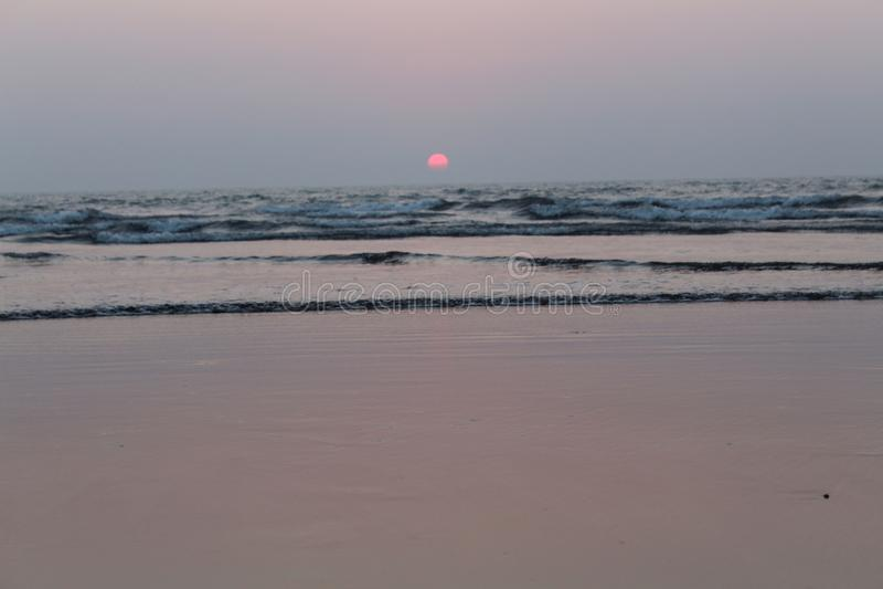 Pic захода солнца на пляже с точным половинным солнцем в воде и половина над водой стоковая фотография rf