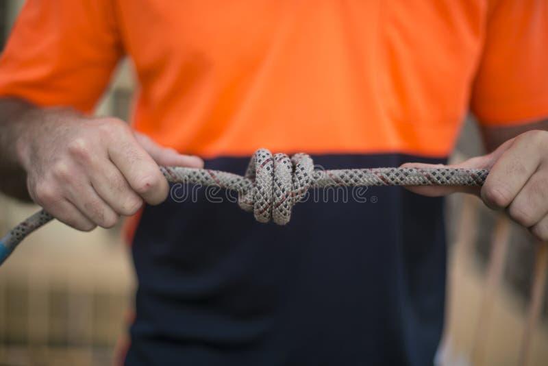 PIC de plan rapproché de travailleur industriel d'accès masculin de corde, inspectant attachant un noeud dans les cordes jumelles image stock