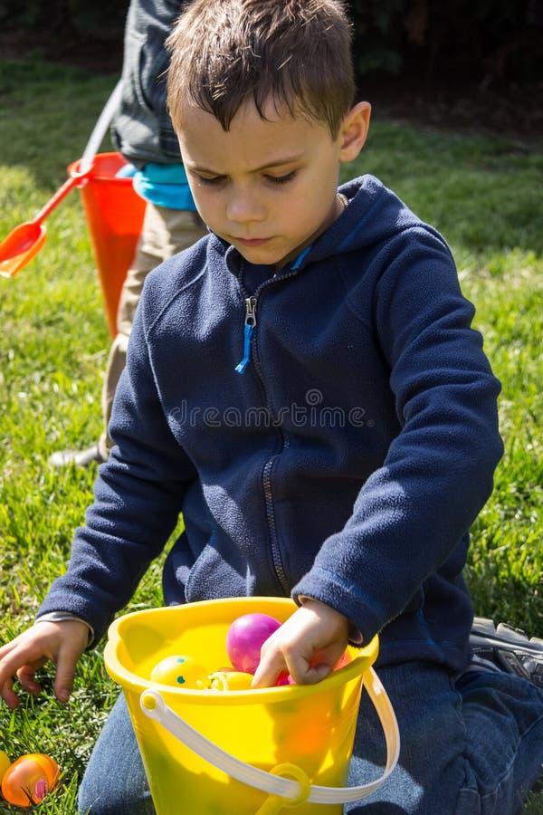 Picaretas novas do menino através de seus ovos da páscoa após um Hu imagens de stock royalty free