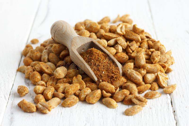 Piccante asciughi le arachidi arrostite su bianco con il mestolo di legno fotografie stock