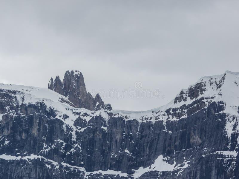 Picchi di montagna ricoperti neve con le nuvole di tempesta fotografie stock