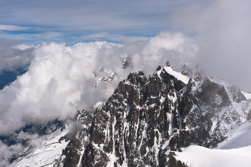 Picchi di montagna Snowbound in nubi immagine stock libera da diritti