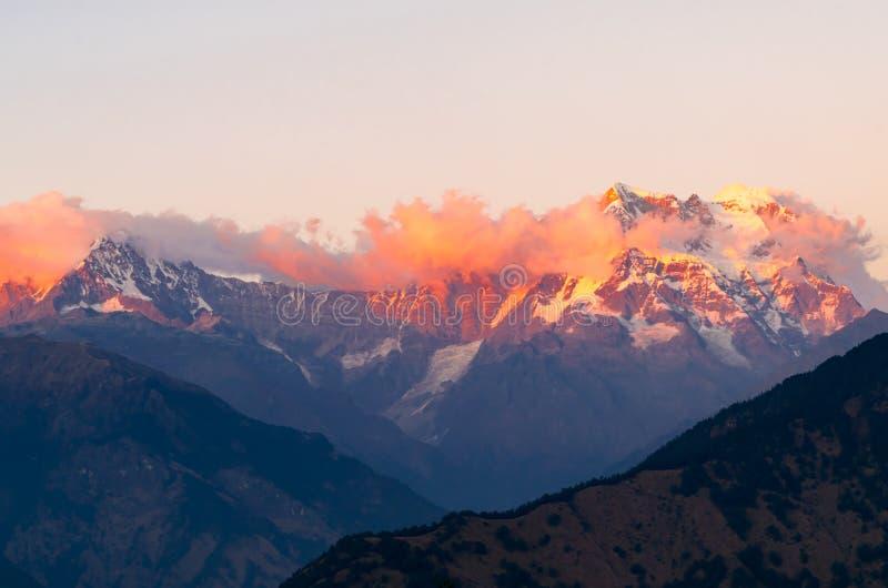 Picchi mistici di Chaukhamba dell'Himalaya di Garhwal durante il tramonto dal campeggio di Deoria Tal fotografia stock libera da diritti