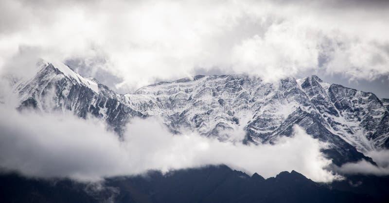 Picchi placcati nevosi di stupore con le nuvole maestose fotografia stock libera da diritti