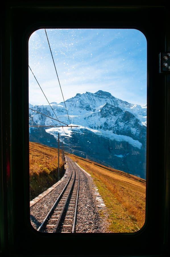 Picco di Jungfrau attraverso la finestra del treno sull'itinerario dalla stazione di Kleine Scheidegg che scala a Jungfraujoch immagine stock
